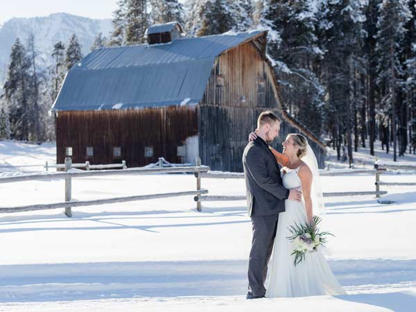 Bride and groom in the snow in front of a barn.